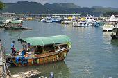 Man enters fishing boat, Sing Kee harbor, Hong Kong, China.