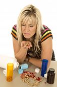 Woman With Pills Spilled And In Hand Face Cringed