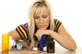 Woman With Spilled Pills Looking Down Serious