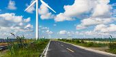 Wind turbines on landscape along empty road against sky.