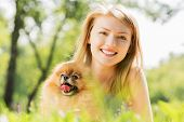 Young pretty girl in summer park with cute dog