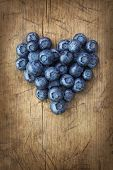 Heart from blackberries on a wooden background