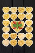 Pasta food selection in heart shaped porcelain dishes with basil herb and red chilli pepper over dark wood background.