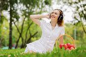 Young attractive girl in summer park wearing headphones