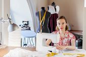 Young attractive woman dressmaker working with sewing machine