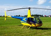 picture of helicopters  - Private yellow helicopter standing on a meadow near the cottages - JPG