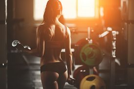 foto of body builder  - Brutal athletic woman pumping up muscles with dumbbells - JPG