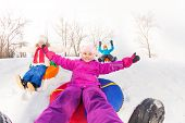 pic of snowy hill  - Girl and kids sliding down the hill on the tubes with arms up during beautiful winter day with trees trunks on the background - JPG
