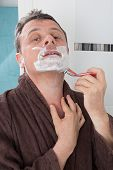 image of shaving  - Man shaving with a razor blade and shaving cream in bathroom - JPG