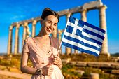 stock photo of poseidon  - Woman holding Greek flag on ancient ruins of Poseidon temple background in Sounion, Greece ** Note: Soft Focus at 100%, best at smaller sizes - JPG