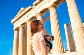 pic of parthenon  - Young and smiling woman photographer taking picture with professional camera of Parthenon temple in Acropolis - JPG