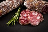 stock photo of salami  - slices of salami on a dark stone board as a background - JPG