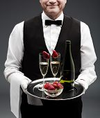 foto of flute  - butler holding tray with two champagne flutes and bottle - JPG