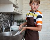 foto of homemaker  - boy doing the dishes in the kitchen