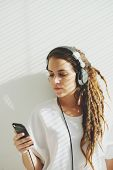 picture of dreadlocks  - Young girl with dreadlocks listening to the music - JPG