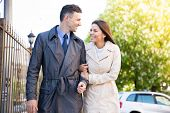 stock photo of flirt  - Smiling young couple walking and flirting outdoors - JPG