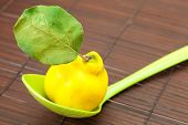 Yellow Quinces With A Green Leaf In A Spoon On A Bamboo Mat