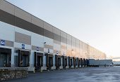 logistic, storage, shipment, transportation and loading concept - warehouse gates and truck loading poster