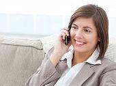 Smilng geschäftsfrau telefonieren auf ihrem Sofa