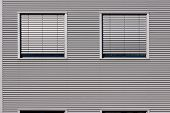Building With Metal Panels And  Two Windows With Persiennes