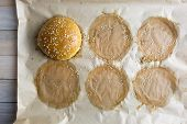 Homemade burger bun on bakery parchment on wooden table. Food photography poster