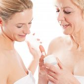 Beauty and skin care - mother and daughter with cream