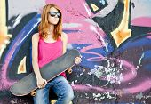 Style Girl With Skateboard Near Graffiti Wall.