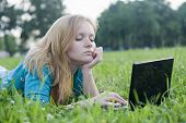 pretty woman with laptop on the green grass