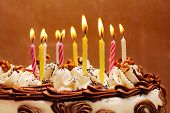 Birthday cake, lit candles on brown background