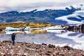 The elderly woman photographs the lagoon. The concept of extreme northern tourism. Ice floes are ref poster