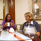 Mulatto Girl And Blond Man Are Drinking Coffee In A Restaurant