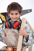 Young boy with adult carpenter's tools