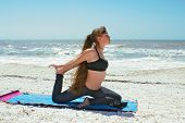 Woman Doing Yoga Exercise On Empty Beach In Kapotasana Or Pigeon Pose