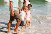 stock photo of holding hands  - Family walking on the beach - JPG