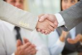Photo of handshake of business partners on background of two partners applauding