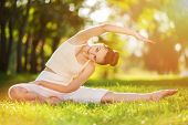 Yoga outdoor. Happy woman doing yoga exercises, meditate in the sunny park. Yoga meditation in natur poster