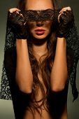 Beautiful sexy woman looking through black openwork lace in darkness