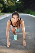 Vertical Shot Confident Young Sporty Female Athlete Sprinter Running With Music In Wired Earphones A poster
