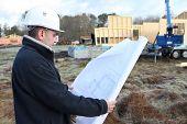 Construction worker examining a blueprint