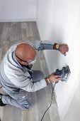 Man using power sander on wall
