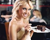 Adorable blond beauty eating a chocolate cake
