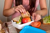 Hands of a woman preparing a lunchbox on the kitchen table