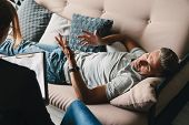 Photo of unshaven casual man lying on sofa and having conversation with psychologist on therapy sess poster