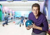 Adult man holding a bowling ball in a bowling alley
