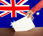 Hand with ballot and box on Flag of Australia