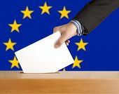 Hand with ballot and box on Flag of Europe
