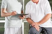 Fitness trainer in gym with clipboard creating training plan for senior man