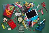 Shopping trolley, computer tablet, calculator, microscope, stationery accessories on green backgroun poster