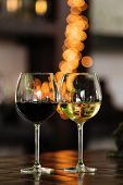 Two Glasses Of Wine White And Red Standing On A Table. Colorful Bokeh. Wine Tastings, Wine Tour. War poster