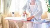 Closeup Of Woman Ironing Clothes On Ironing Board poster